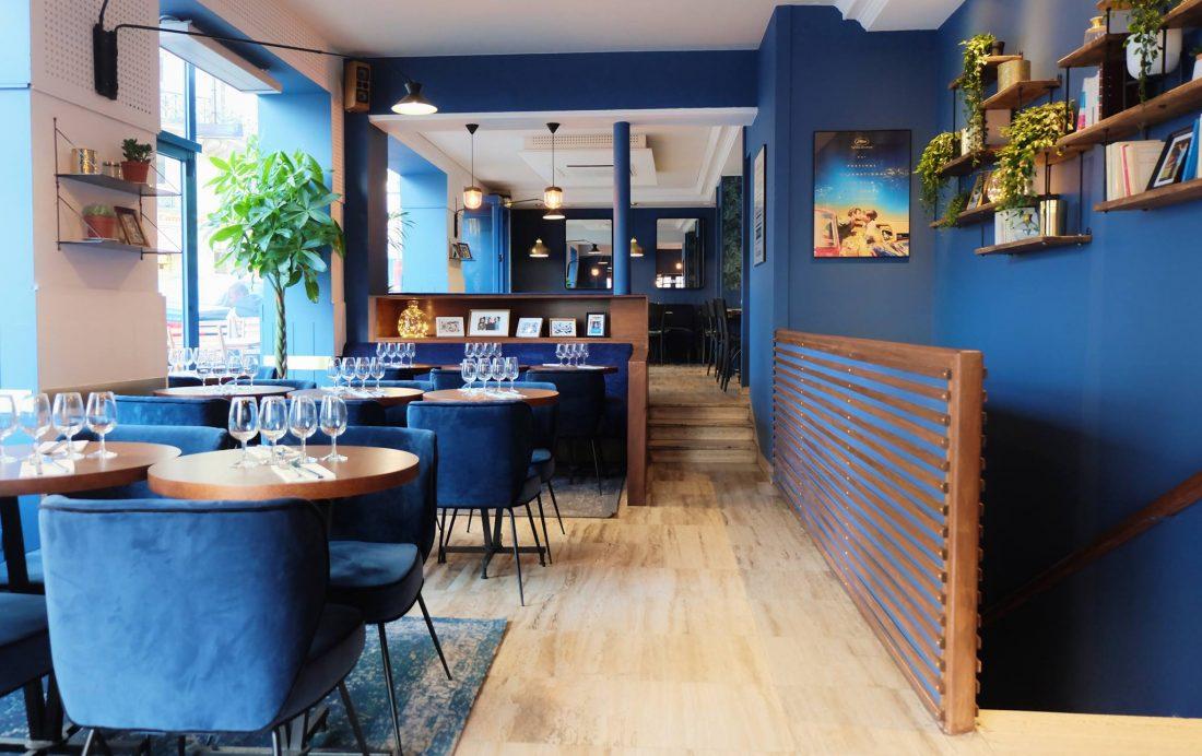 Une grande salle au ton bleu, de grandes baies donnant sur la rue, et de confortables fauteuils en velours font de L'invitée un endroit fort agréable...